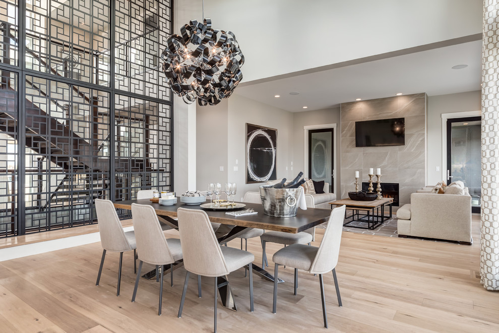 Large contemporary open plan dining room in Calgary with white walls, light hardwood flooring, a standard fireplace and a tiled fireplace surround.