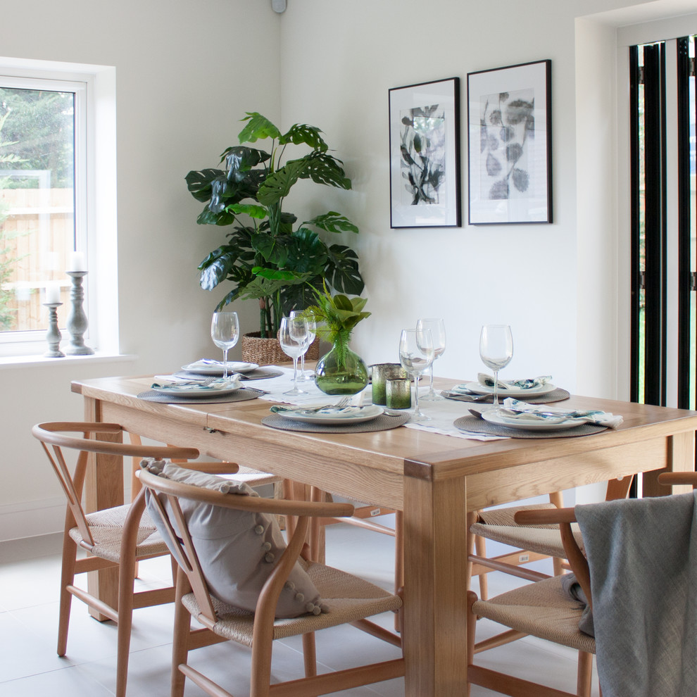 Design ideas for a medium sized contemporary enclosed dining room in Hertfordshire with white walls and white floors.