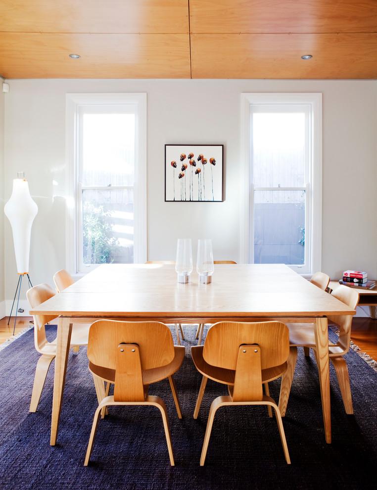 Dining room - mid-sized mid-century modern medium tone wood floor dining room idea in Sydney with white walls