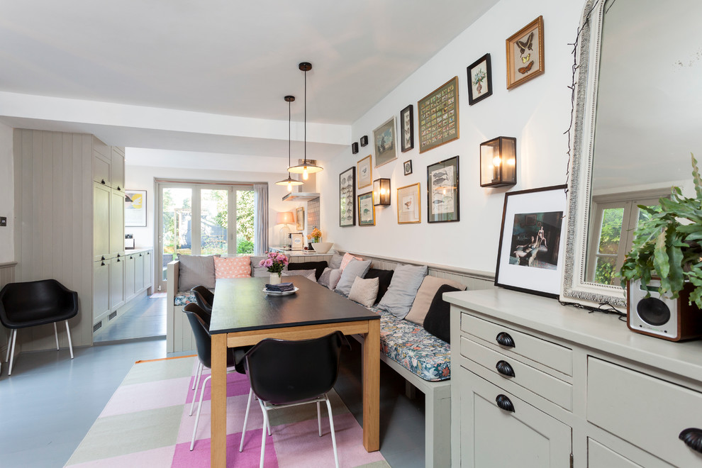 Dining room - scandinavian painted wood floor dining room idea in London with white walls