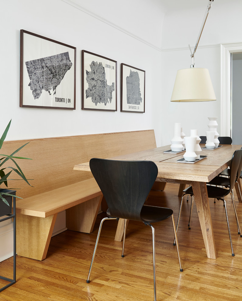 Example of a mid-sized danish light wood floor and beige floor enclosed dining room design in Toronto with white walls and no fireplace