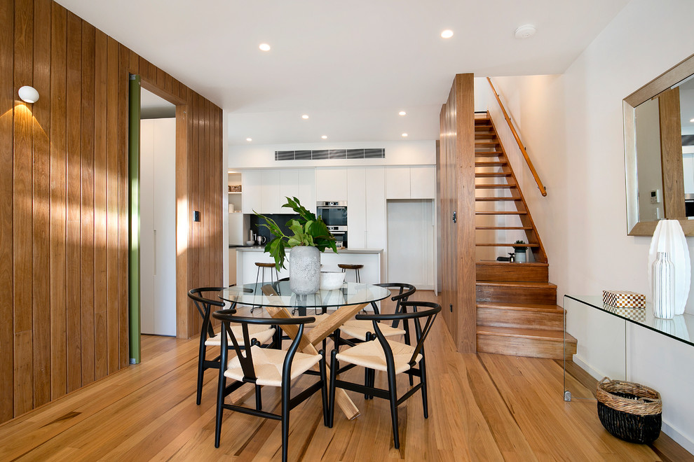 Example of a trendy medium tone wood floor kitchen/dining room combo design in Sydney with white walls and no fireplace
