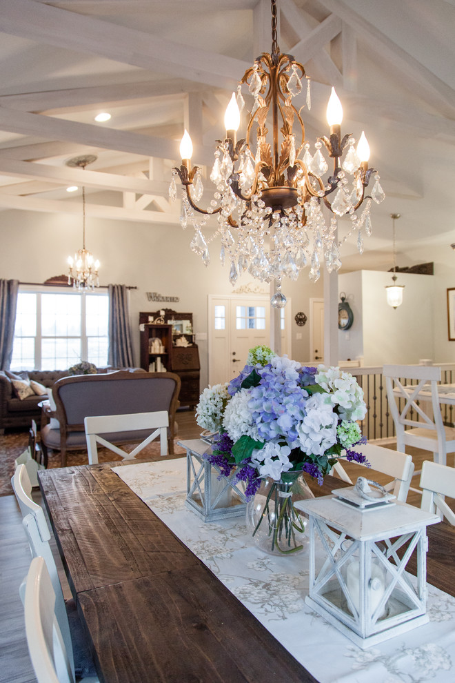 Example of a mid-sized cottage chic light wood floor and multicolored floor great room design in Other with white walls and no fireplace