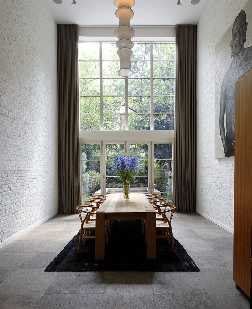 Dining room - contemporary slate floor dining room idea in New York with white walls