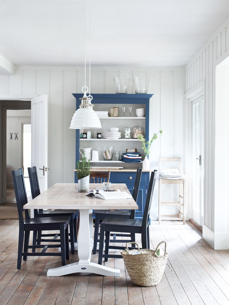 Inspiration for a scandinavian light wood floor dining room remodel in London with white walls and no fireplace