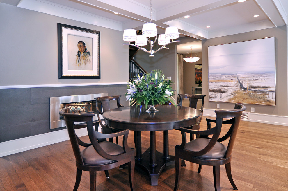 Transitional medium tone wood floor dining room photo in Calgary with gray walls