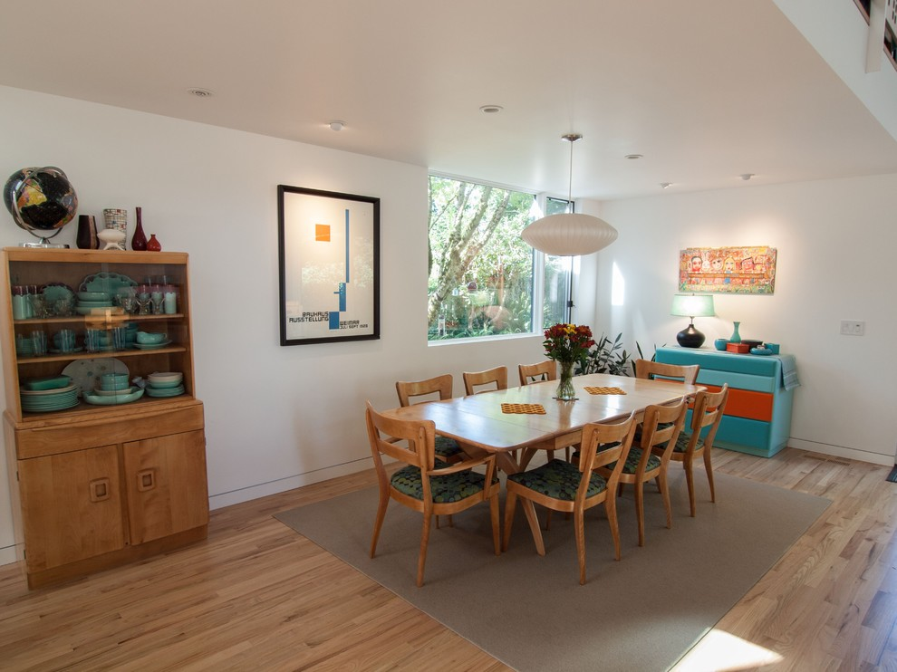 Example of a trendy medium tone wood floor dining room design in Portland with white walls