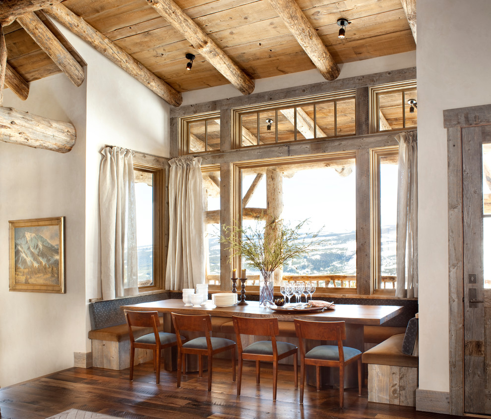 Example of a mountain style dark wood floor dining room design in Other with white walls