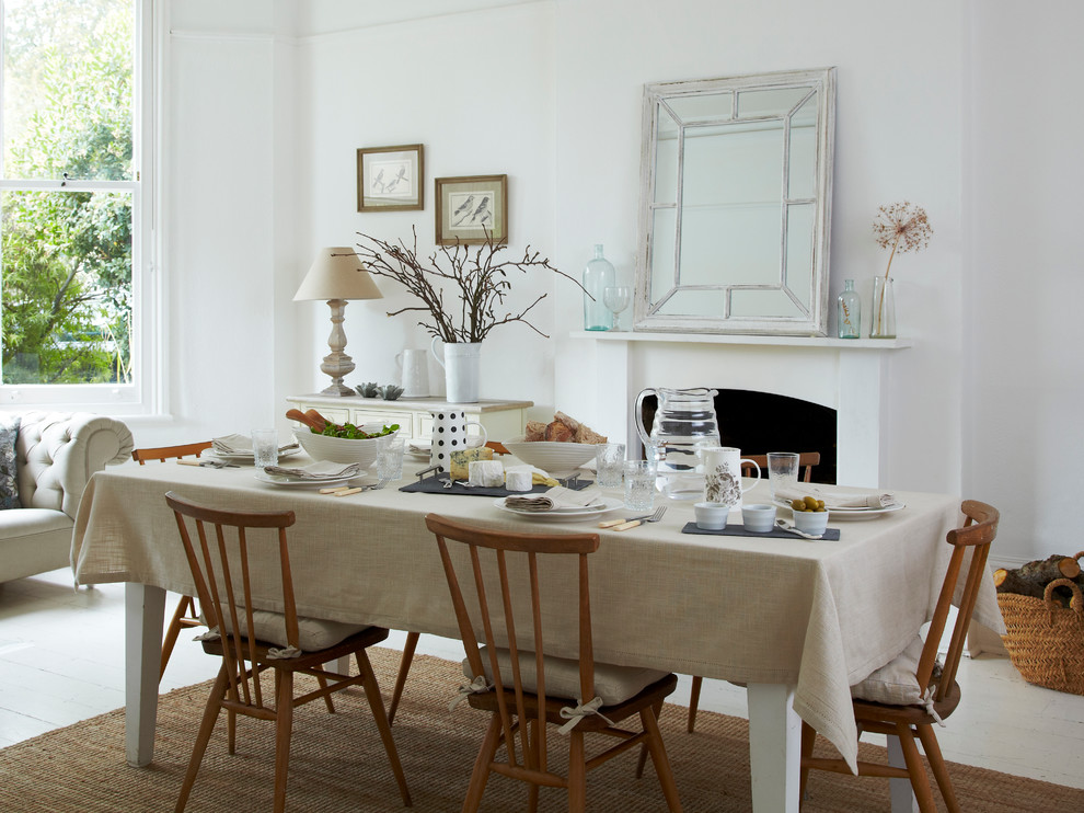 Example of a large danish light wood floor dining room design in London with white walls, a standard fireplace and a plaster fireplace