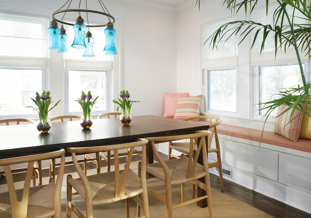 Inspiration for a small coastal dark wood floor and brown floor enclosed dining room remodel in Newark with white walls