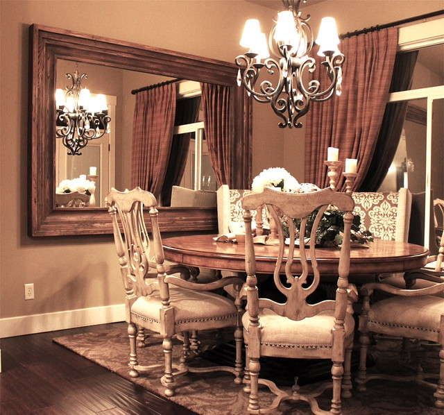 large wood-framed mirror mounted on the dining room wall | dining