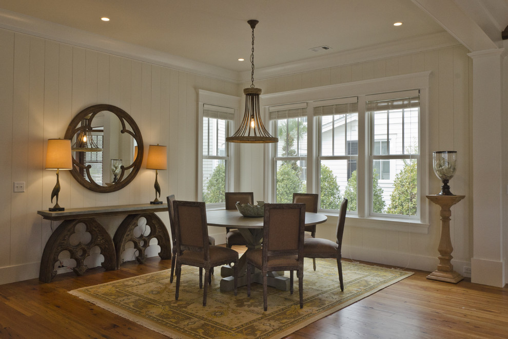 Example of a mountain style medium tone wood floor dining room design in Charleston with white walls
