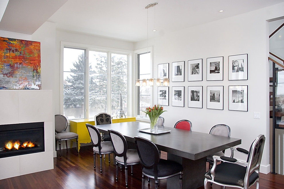 Example of a trendy dining room design in Calgary with a tile fireplace and white walls