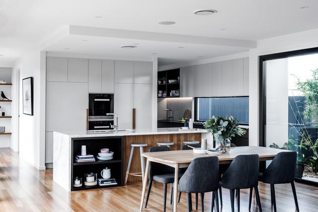 Foto di una sala da pranzo aperta verso il soggiorno contemporanea con pareti bianche, pavimento in legno massello medio, nessun camino e pavimento beige