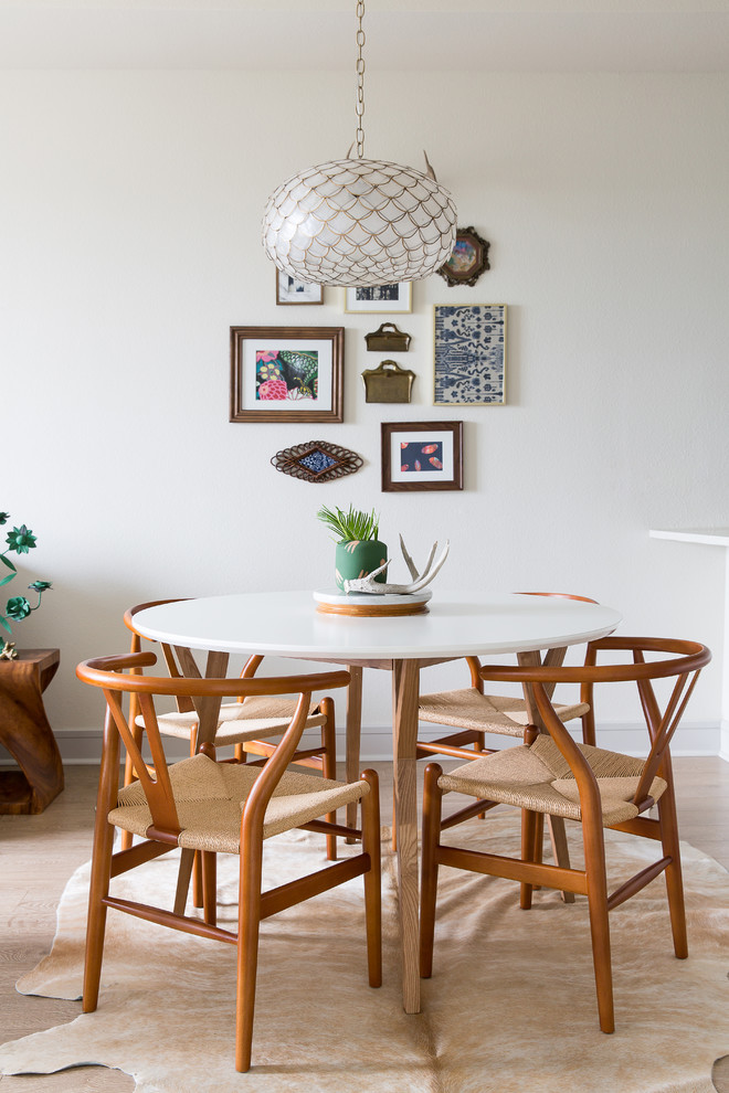 Example of an eclectic light wood floor dining room design in New Orleans with white walls