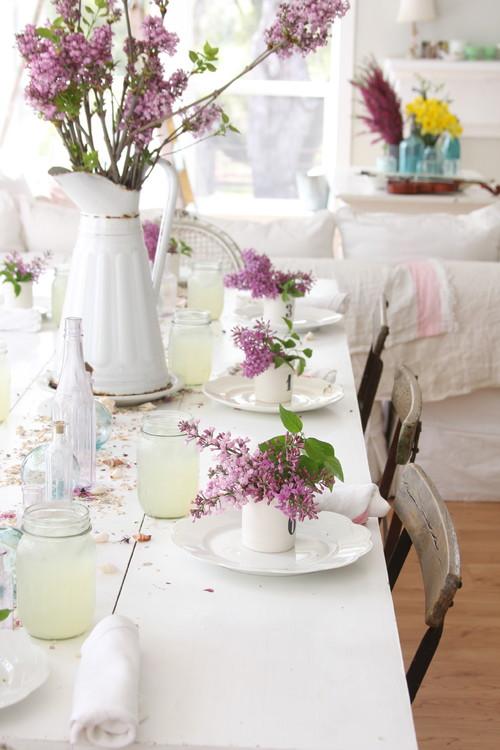 真っ白なテーブルに春らしいお花を飾り、ぱらぱら落ちた花びらからもあたたかさを感じるテーブルに。お花から漂う香り・天然なアロマに癒されそうですね♡