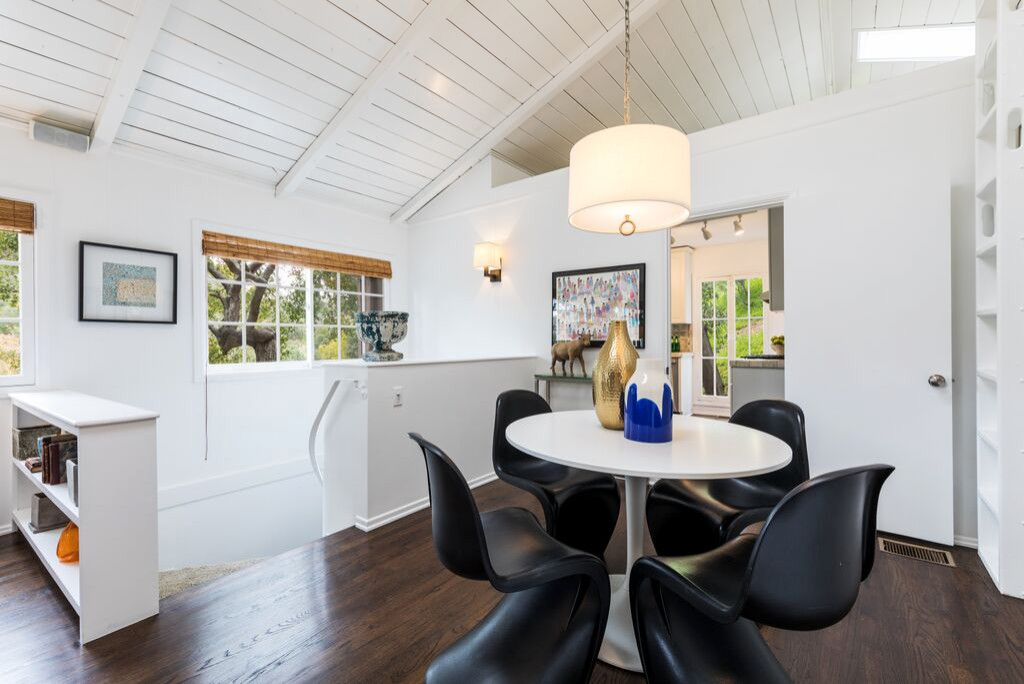 Example of a small minimalist dark wood floor and brown floor great room design in Los Angeles with white walls and no fireplace