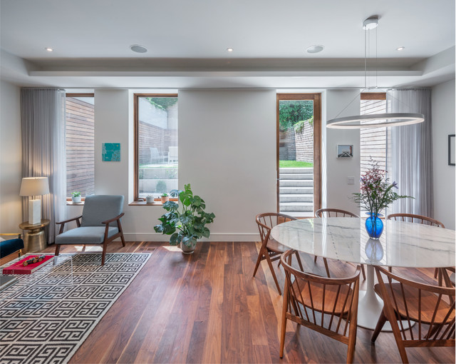 Dining room - transitional dark wood floor and brown floor dining room idea in New York with white walls