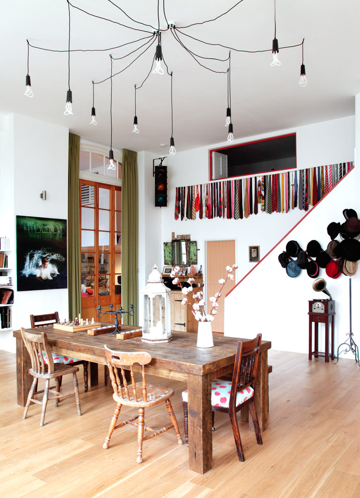 Inspiration for a large eclectic light wood floor dining room remodel in London with white walls and no fireplace