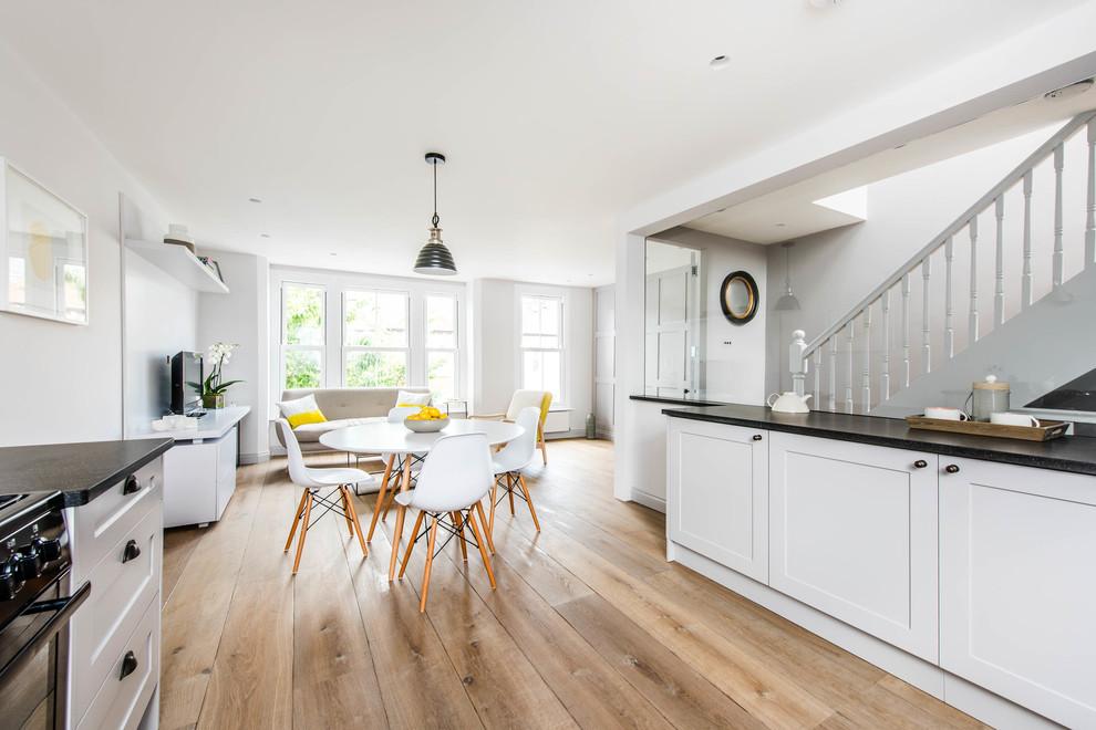 Diseño de comedor nórdico, abierto, con paredes blancas y suelo de madera clara