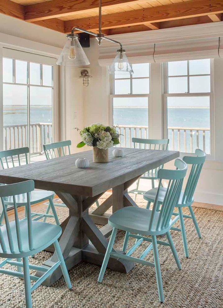 Example of a mid-sized beach style light wood floor dining room design in Boston with white walls