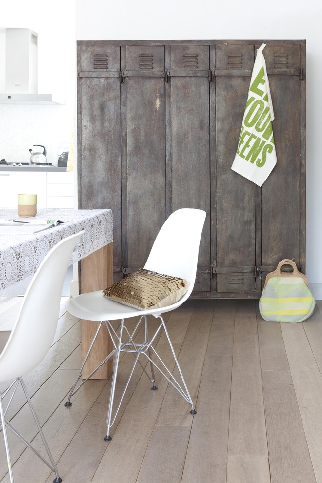 Example of a cottage chic medium tone wood floor dining room design in Amsterdam with white walls