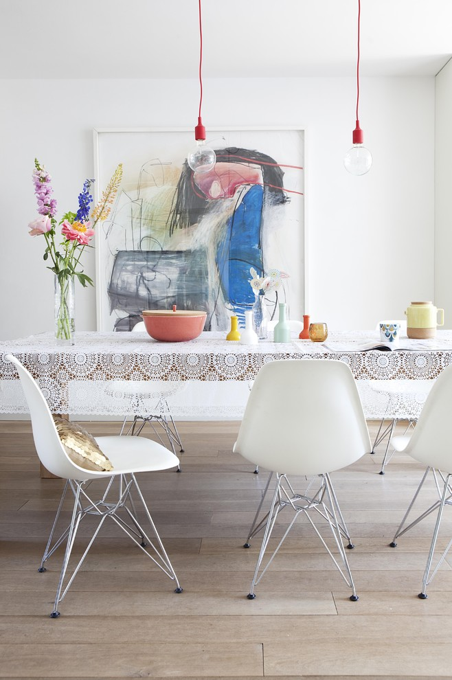 Example of a minimalist light wood floor dining room design in Amsterdam with white walls