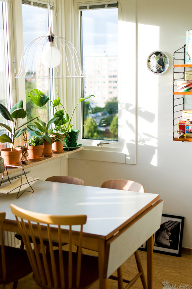 Example of a small 1960s medium tone wood floor dining room design in Malmo with white walls