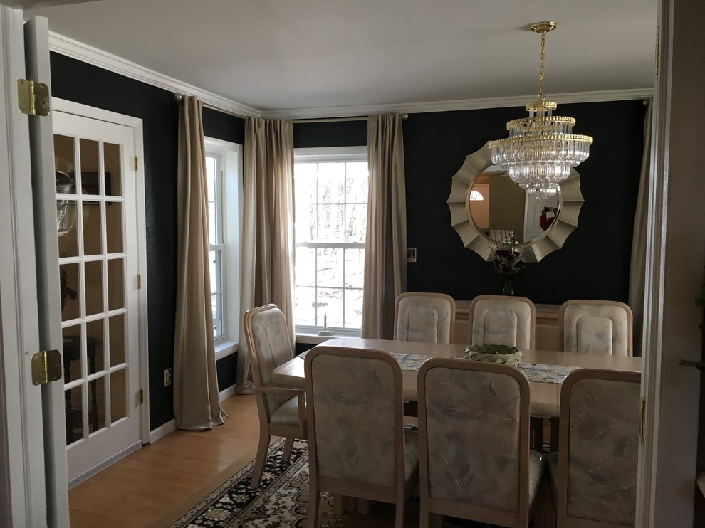 Example of a mid-sized minimalist light wood floor enclosed dining room design in Boston with black walls