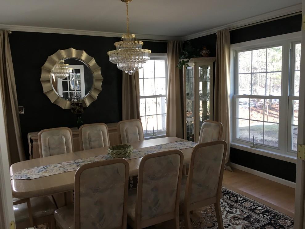 Mid-sized minimalist light wood floor enclosed dining room photo in Boston with black walls