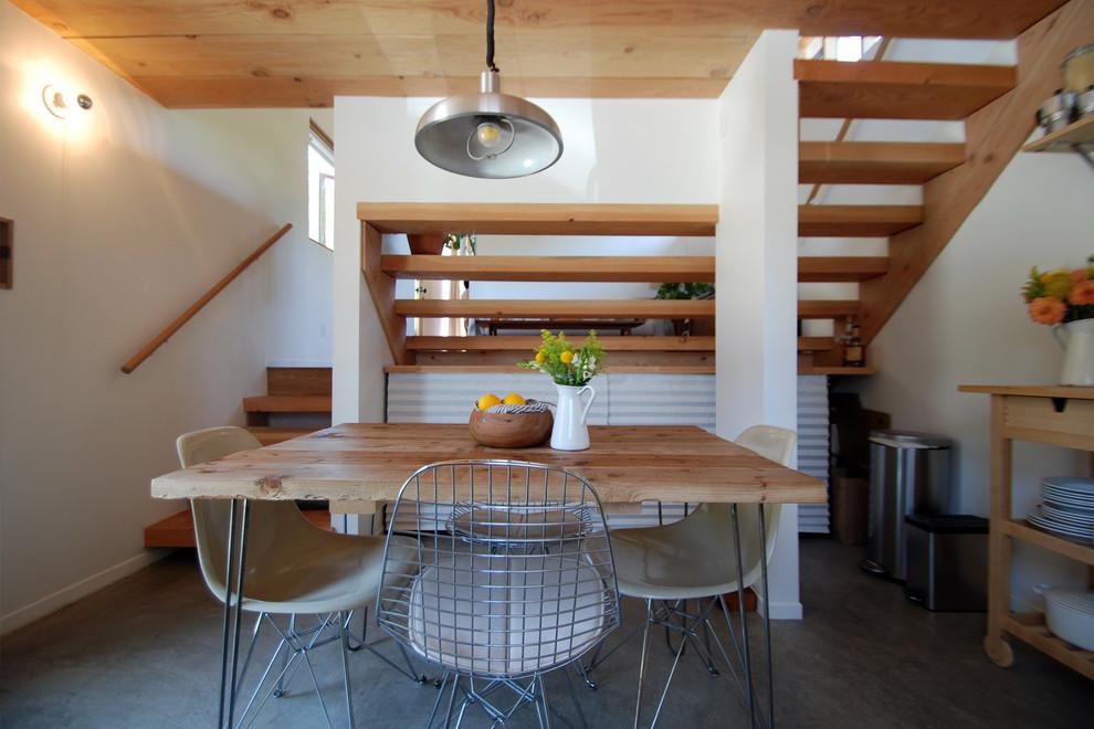 Immagine di una sala da pranzo moderna chiusa e di medie dimensioni con pareti bianche, pavimento in cemento, nessun camino e pavimento bianco