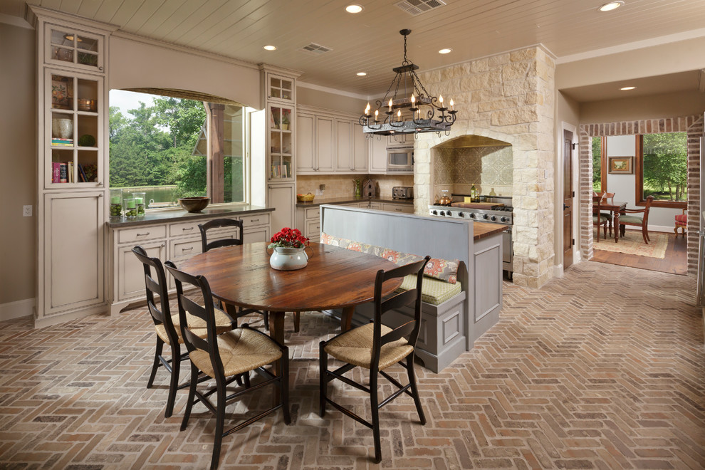 Example of a large tuscan brick floor and brown floor kitchen/dining room combo design in Houston with beige walls