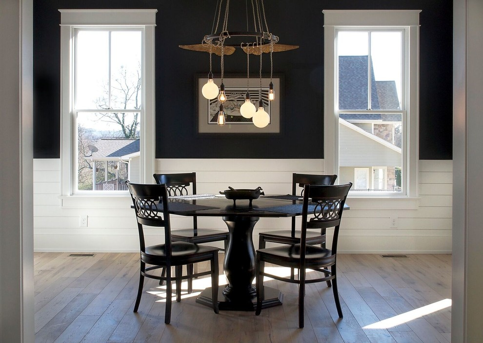 Mid-sized farmhouse light wood floor and brown floor enclosed dining room photo in Other with black walls and no fireplace