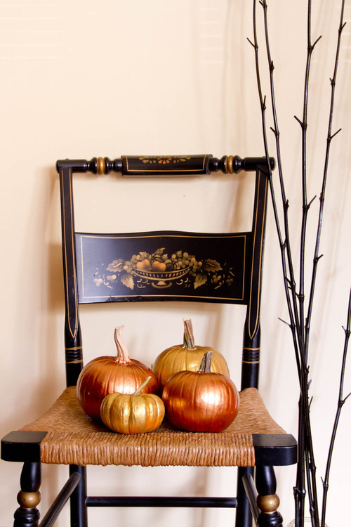 four metallic painted pumpkins on a chair