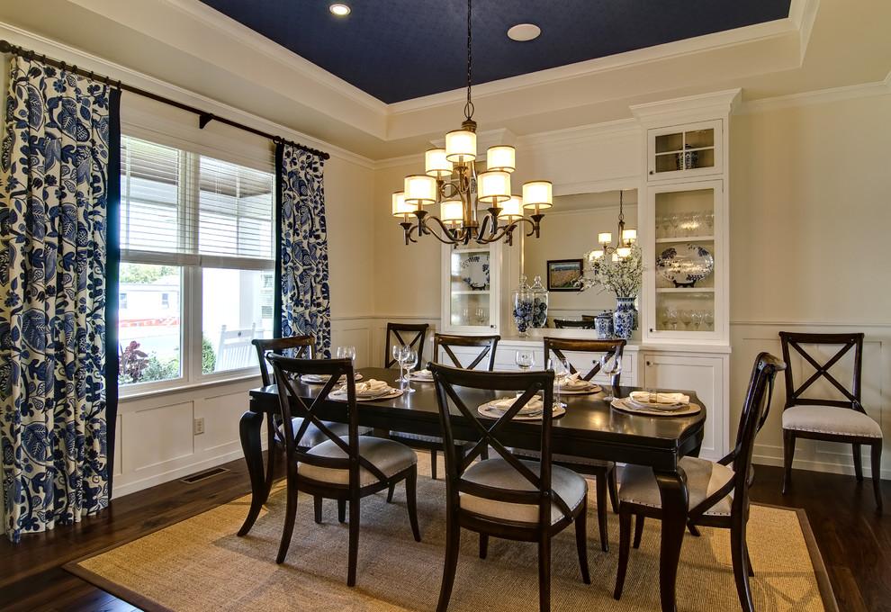 Imagen de comedor clásico con paredes beige y suelo de madera oscura