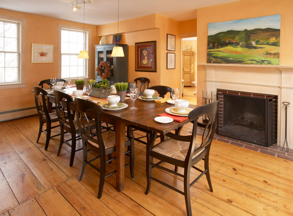 Farmhouse dining room photo in Boston with a brick fireplace and orange walls