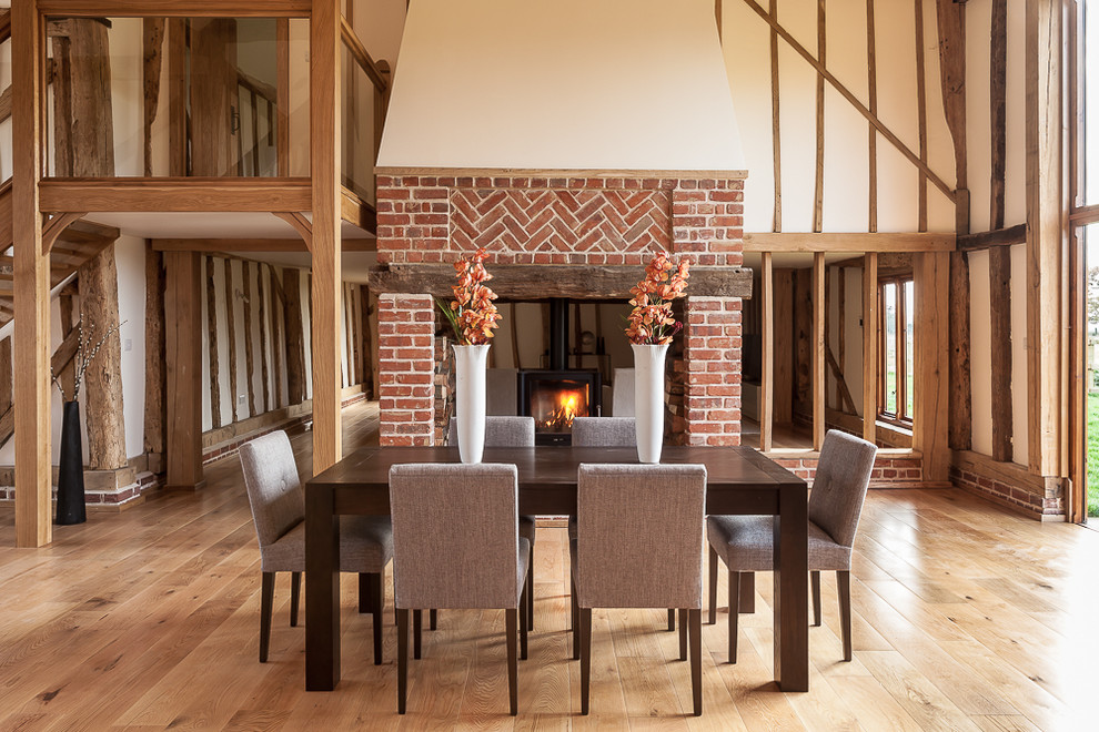 Inspiration for a farmhouse medium tone wood floor great room remodel in London with beige walls