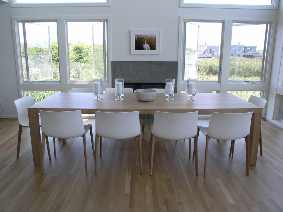Inspiration for a large contemporary light wood floor dining room remodel in New York with white walls, a standard fireplace and a stone fireplace