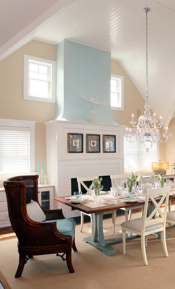 Example of a coastal dining room design in Philadelphia with beige walls and a brick fireplace