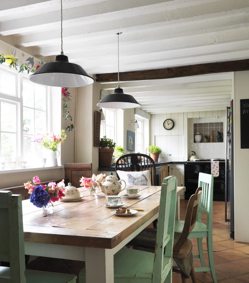 Example of a cottage chic terra-cotta floor kitchen/dining room combo design in London