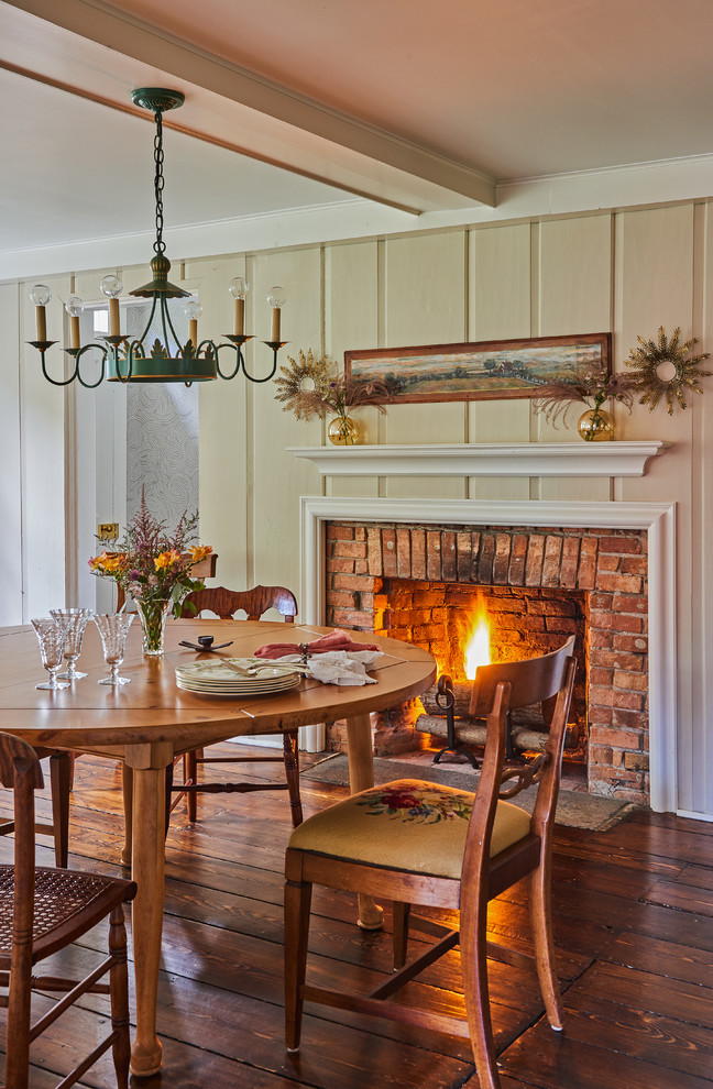 Kitchen/dining room combo - large country dark wood floor and brown floor kitchen/dining room combo idea in New York with beige walls, a standard fireplace and a brick fireplace