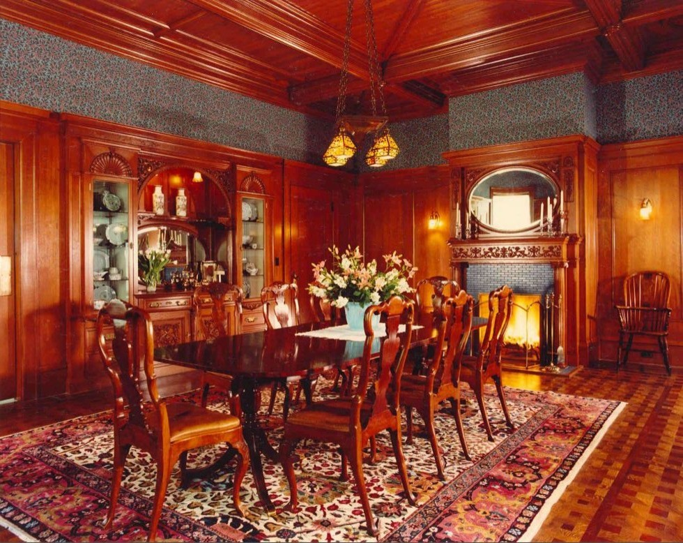 Formal dining room with wood panel walls and detailed wood celling