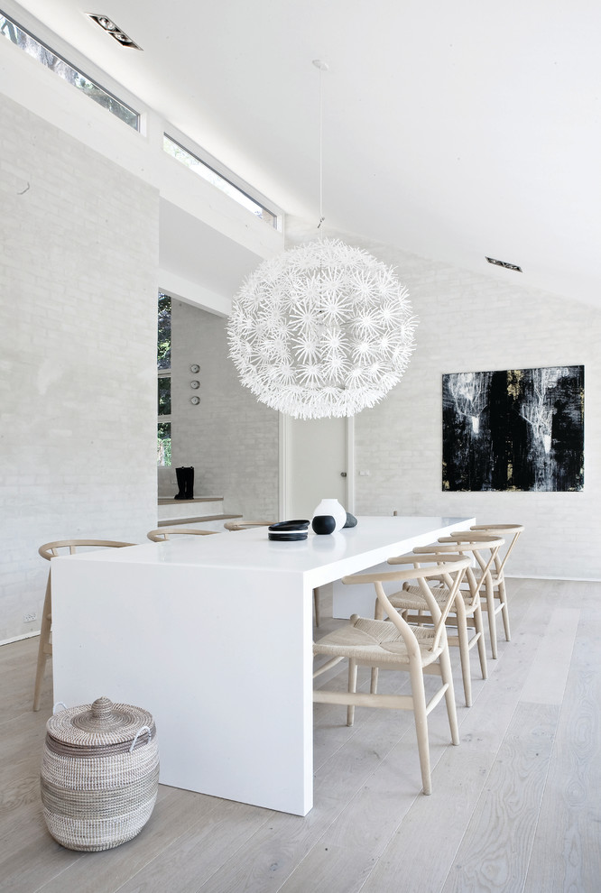 Example of a large danish painted wood floor enclosed dining room design in Copenhagen with white walls