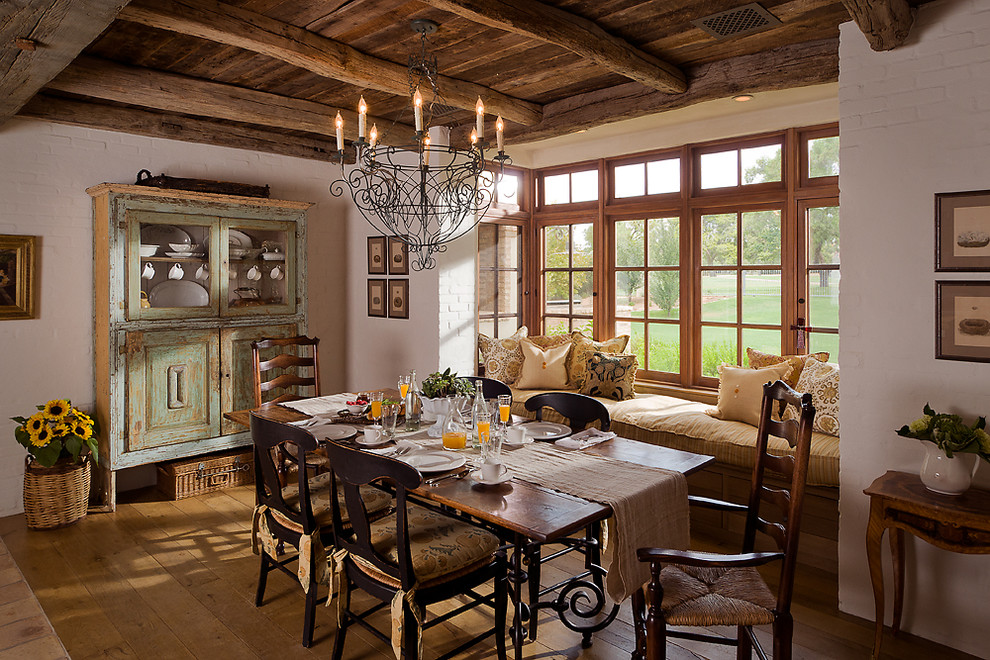 Dining room - french country medium tone wood floor dining room idea in Phoenix with white walls
