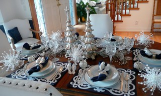 a tablescape featuring silver tree figures and eclectic pieces