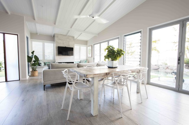 Inspiration for a mid-sized beach style open plan dining in Gold Coast - Tweed with white walls, painted wood floors, a standard fireplace, a stone fireplace surround and grey floor.