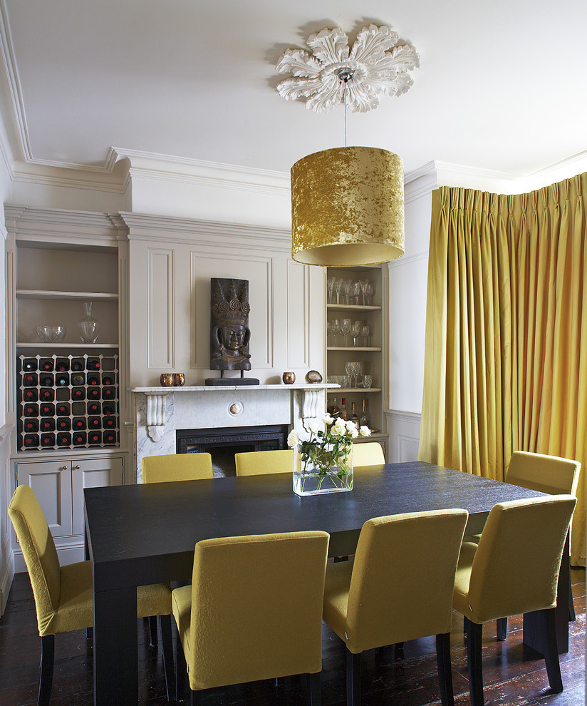 Trendy dark wood floor dining room photo in Dublin with white walls and a standard fireplace