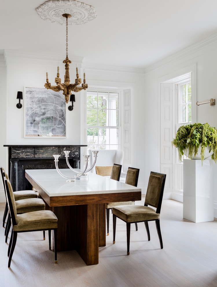 Enclosed dining room - transitional light wood floor and gray floor enclosed dining room idea with white walls, a standard fireplace and a stone fireplace