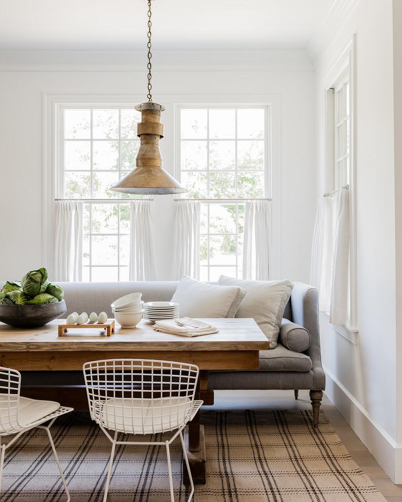 Dining room - coastal light wood floor dining room idea with white walls