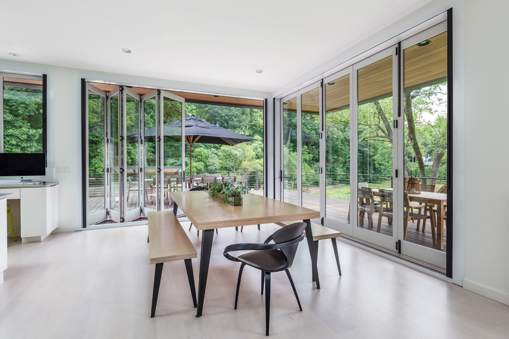 Dining room - contemporary light wood floor dining room idea in Charleston with white walls
